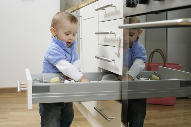 Baby boy emptying a kitchen drawer